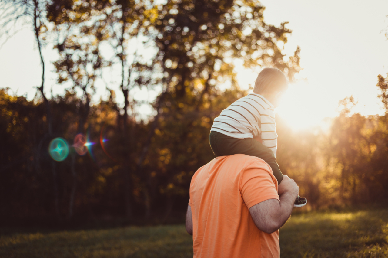Man with son on shoulders walking away towards sunlight.